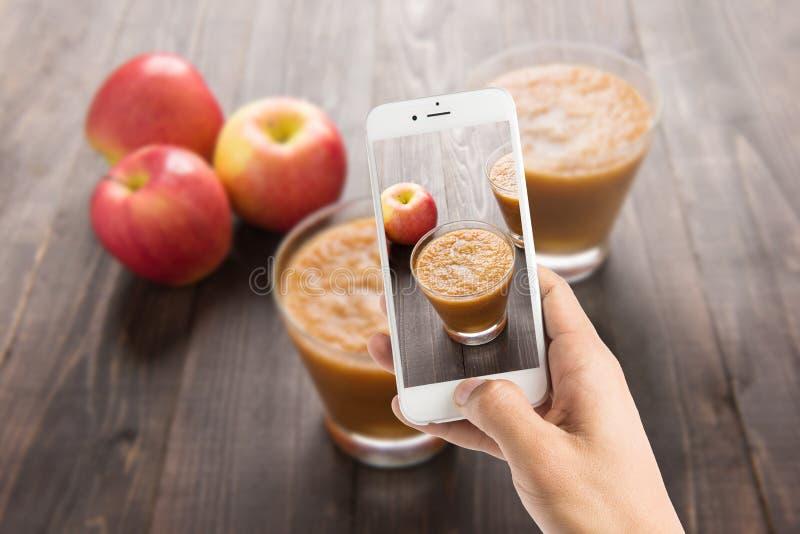 Het nemen van foto van rode appelen smoothie op Houten achtergrond stock foto