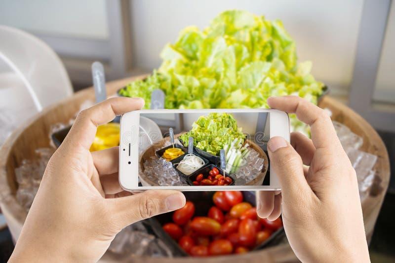 Het nemen van foto van saladebar met groenten in het restaurant stock fotografie