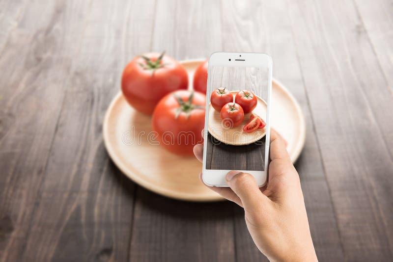 Het nemen van foto van tomaten op de oude houten lijst stock foto
