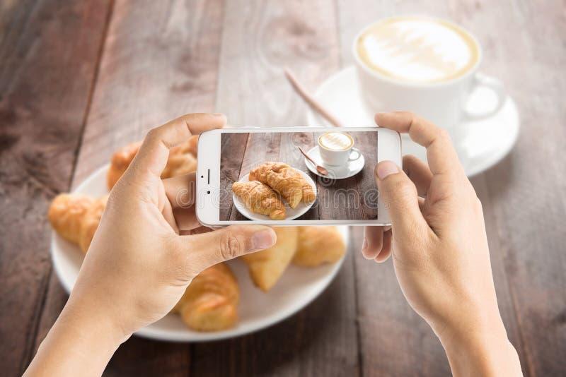 Het nemen van foto van verse gebakken croissants en koffie op houten lijst royalty-vrije stock fotografie