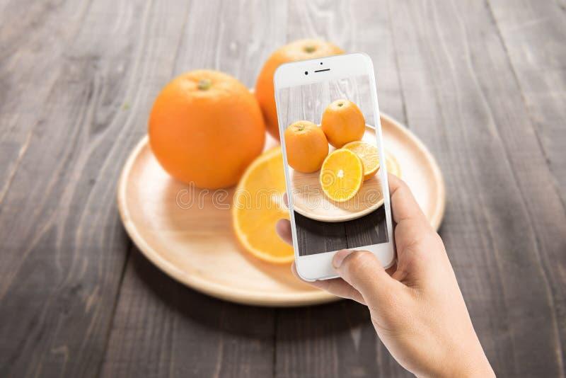 Het nemen van foto van verse sinaasappelen op houten schotel, verse vruchten op wo royalty-vrije stock foto's