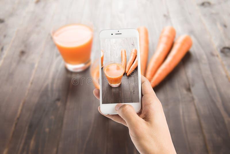 Het nemen van foto van wortelsap op houten achtergrond royalty-vrije stock afbeelding