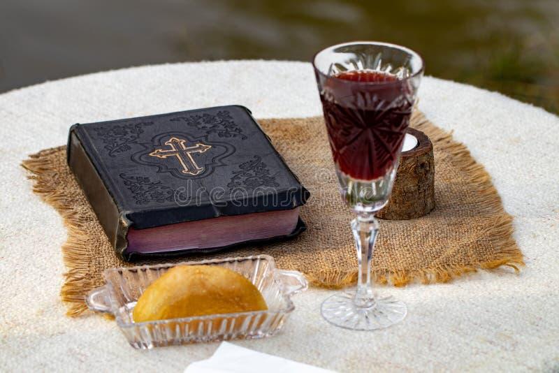 Het nemen van Heilige Communie Kop van glas met rode wijn, brood en Heilige Slab royalty-vrije stock fotografie