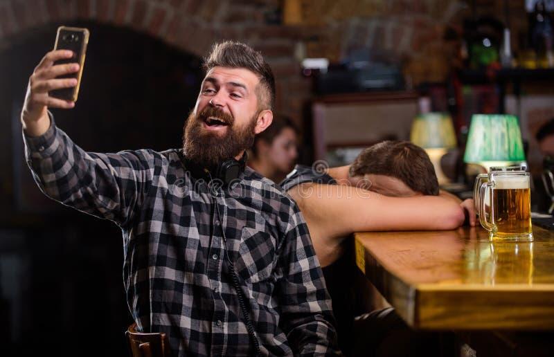 Het nemen van selfie concept Online mededeling Verzend selfie naar vrienden sociale netwerken Mens in bar het drinken bier neem stock fotografie