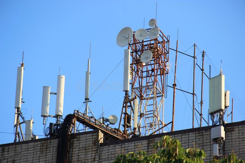 Het netwerkrepeaters van telecommunicatiebasisstations op het dak van het gebouw De cellulaire communicatie antenne op een de bou royalty-vrije stock foto