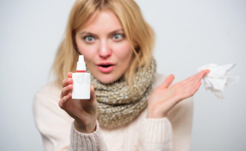 Het neusnevel gebruiken Leuke vrouw die neuskoude of allergie verzorgen Ongezond meisje met lopende neus die neusnevel gebruiken  royalty-vrije stock afbeelding