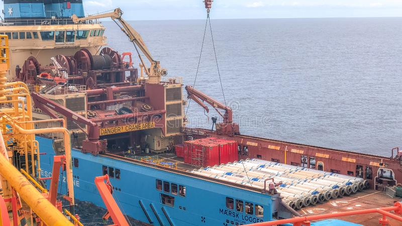 Het Newest Maersk Company Anker die Zeeleveringsschip dicht bij de zeeboringsinstallatie behandelen nam in ladingsverrichtingen i stock foto