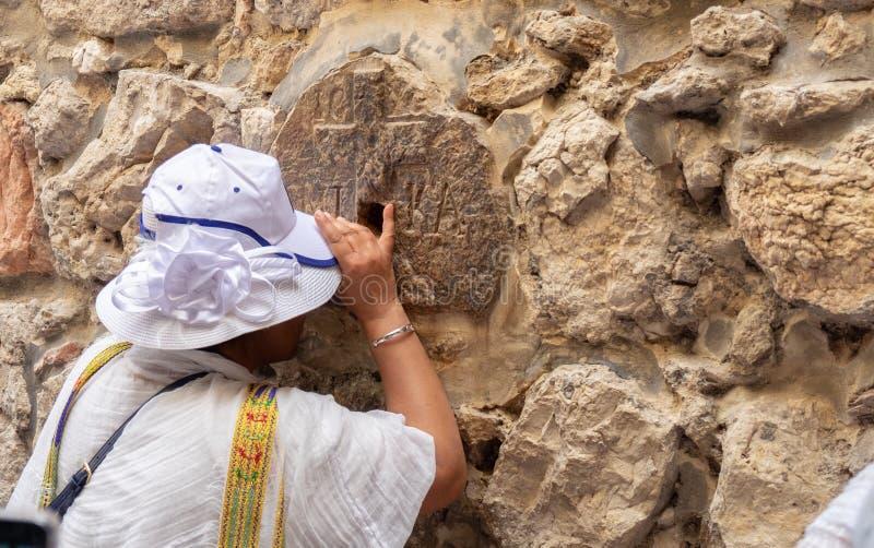 Het niet gedefiniëerde Orthodoxe Christelijke meisje bidt bij Achtste Post van Via Dolorosa De Oude Stad van Jeruzalem royalty-vrije stock fotografie