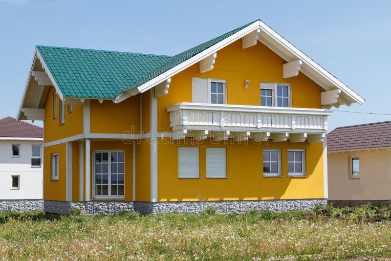 Het nieuwe gele huis met witte vensters en een groot houten balkon bouwden het dorp in stock fotografie