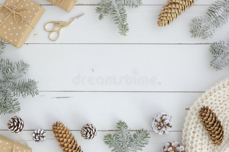 Het nieuwe jaar, Kerstmis, vrolijk Kerstmiskader van decoratie, sparappel en tak, breide sjaal, giftdoos, gouden schaar stock afbeeldingen