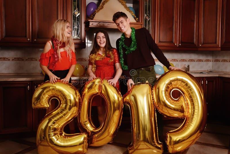 Het nieuwe jaar van 2019 komt De groep vrolijke jongeren die gouden gekleurde aantallen dragen en heeft pret bij de partij stock foto