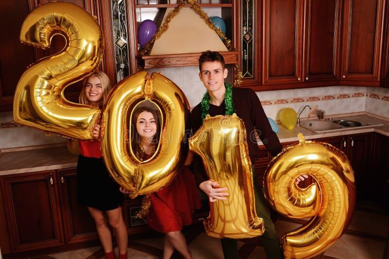 Het nieuwe jaar van 2019 komt De groep vrolijke jongeren die gouden gekleurde aantallen dragen en heeft pret bij de partij royalty-vrije stock fotografie