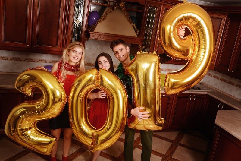 Het nieuwe jaar van 2019 komt De groep vrolijke jongeren die gouden gekleurde aantallen dragen en heeft pret bij de partij stock afbeelding