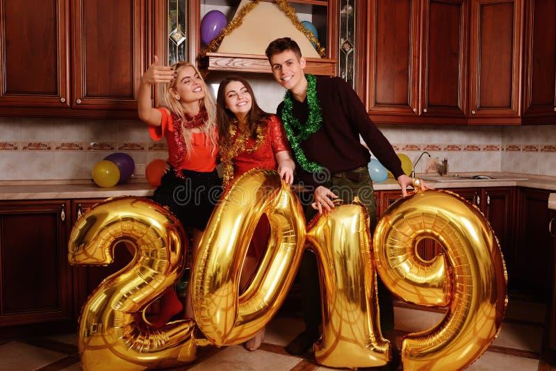 Het nieuwe jaar van 2019 komt De groep vrolijke jongeren die gouden gekleurde aantallen dragen en heeft pret bij de partij royalty-vrije stock afbeelding