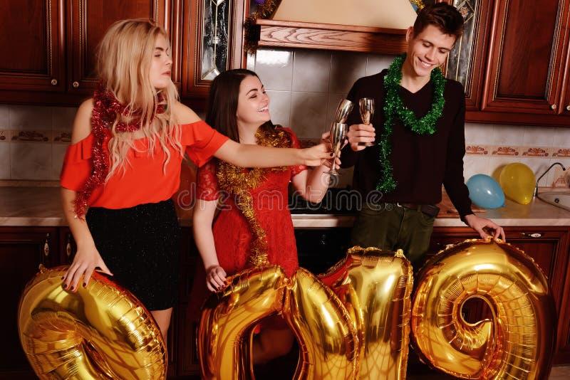 Het nieuwe jaar van 2019 komt De groep vrolijke jongeren die gouden gekleurde aantallen dragen en heeft pret bij de partij stock foto's
