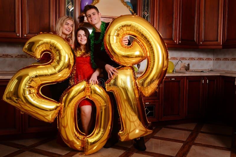 Het nieuwe jaar van 2019 komt De groep vrolijke jongeren die gouden gekleurde aantallen dragen en heeft pret bij de partij royalty-vrije stock afbeeldingen