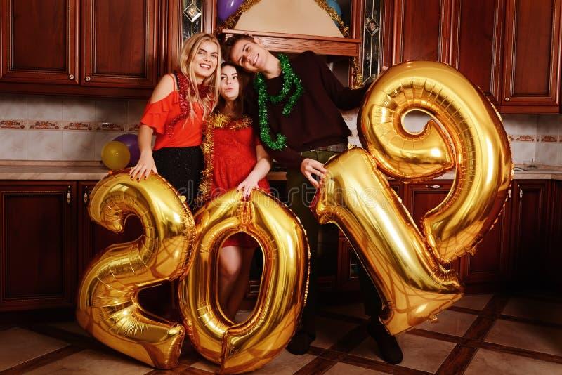 Het nieuwe jaar van 2019 komt De groep vrolijke jongeren die gouden gekleurde aantallen dragen en heeft pret bij de partij stock fotografie