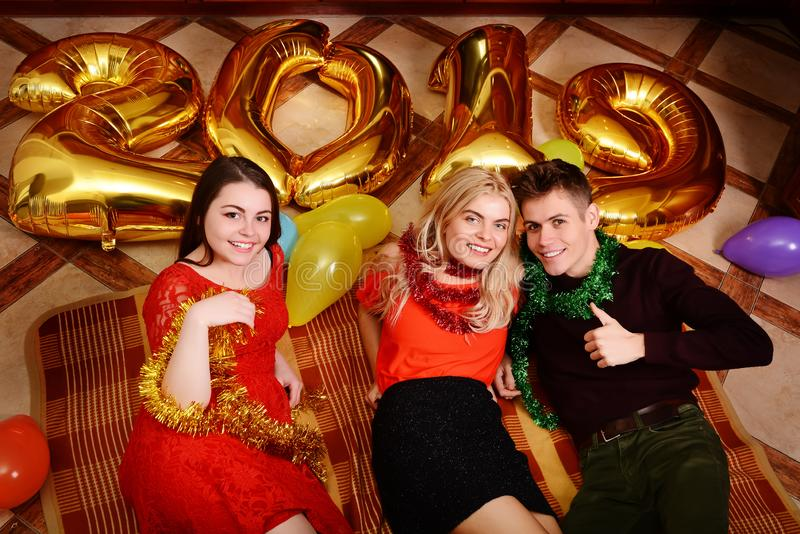 Het nieuwe jaar van 2019 komt De groep vrolijke jongeren die gouden gekleurde aantallen dragen en heeft pret bij de partij royalty-vrije stock foto's