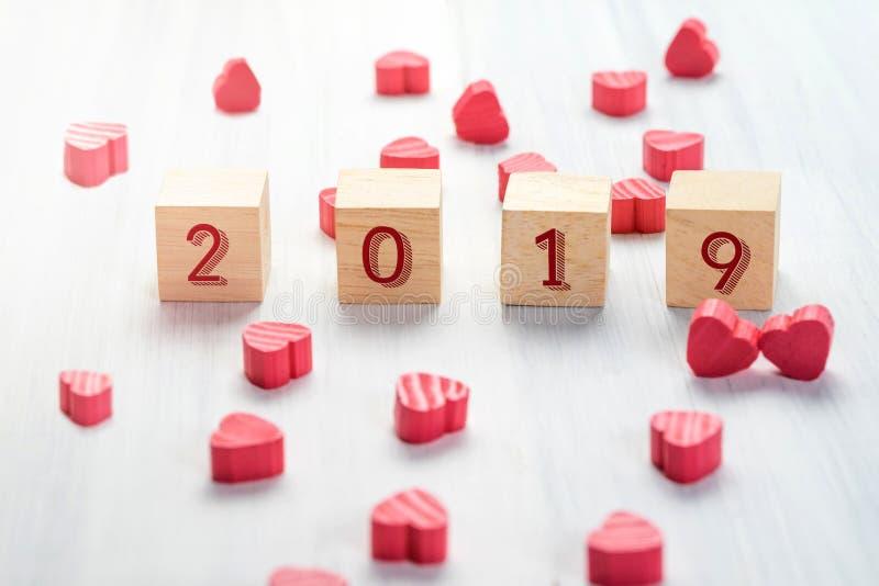 het nieuwe jaar van 2019 op houten kubus met groep mini rood hart op wit stock fotografie