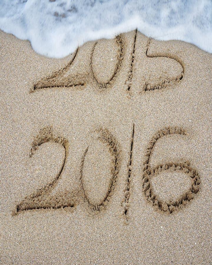 Het nieuwe jaar 2016 vervangt 2015 op zandstrand stock foto