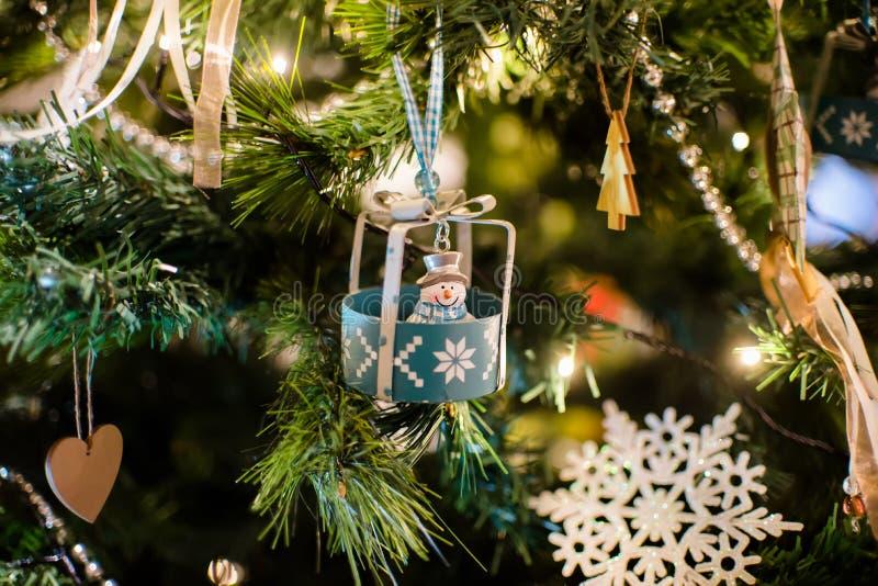 Het nieuwe jaarstuk speelgoed sneeuwman hangen op een verfraaide Kerstboom stock afbeeldingen