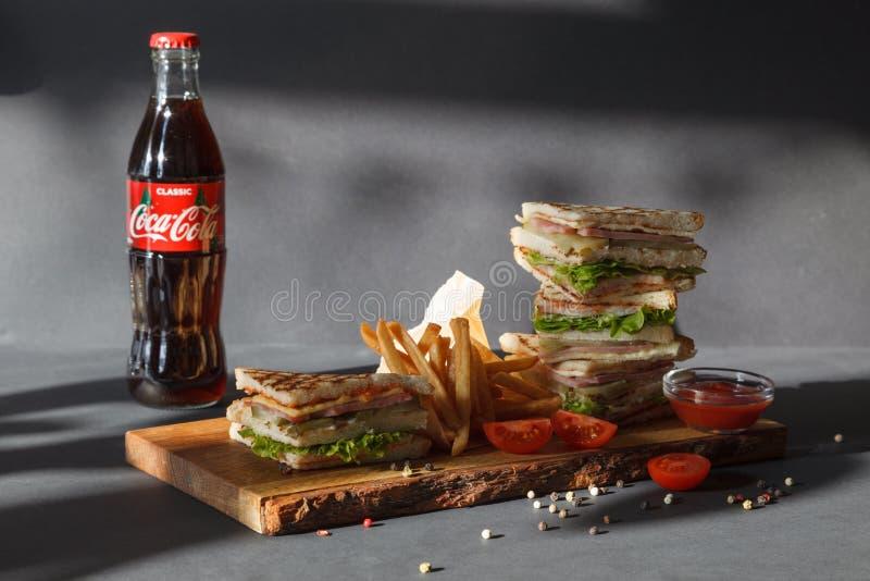 Het nieuwe menu van de fotozitting van koffiehuis, verse dubbeldekker, de Coca-cola van de glasfles, frieten en ketchup op houten stock foto