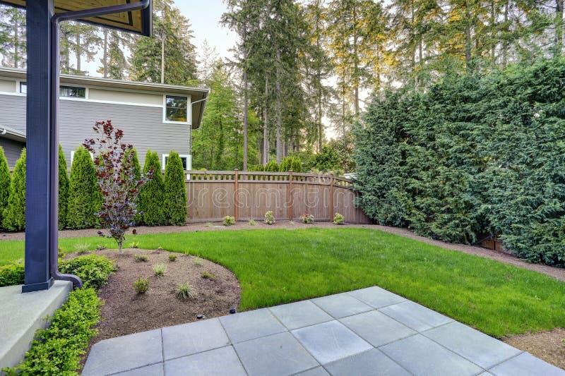 Het nieuwe moderne huis kenmerkt een binnenplaats met mooie tuin stock foto's