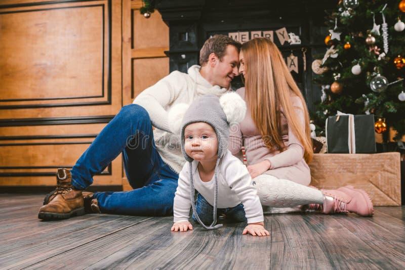 Het Nieuwjaar en Kerstmis van de familievakantie De jonge Kaukasische de papazoon van het familiemamma 1 jaar zit houten vloer di stock foto