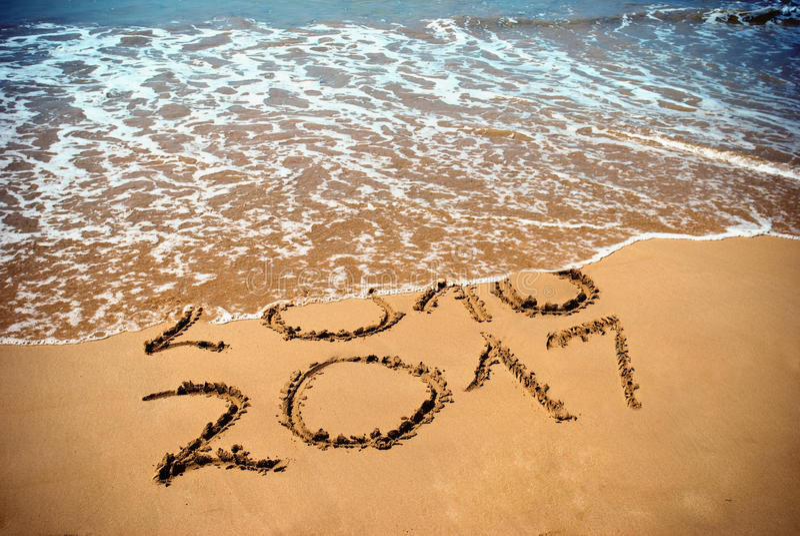 Het nieuwjaar 2017 is komend concept - de inschrijving 2017 en 2016 op een strandzand, de golf behandelt cijfers 2016 Nieuwjaar 2 royalty-vrije stock afbeelding