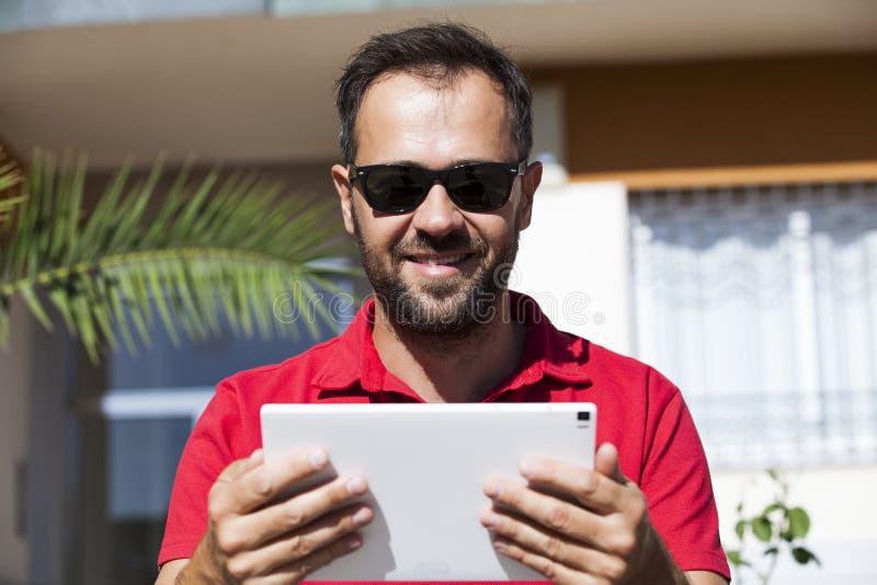 Het nieuws van de mensenlezing in een tablet stock foto's