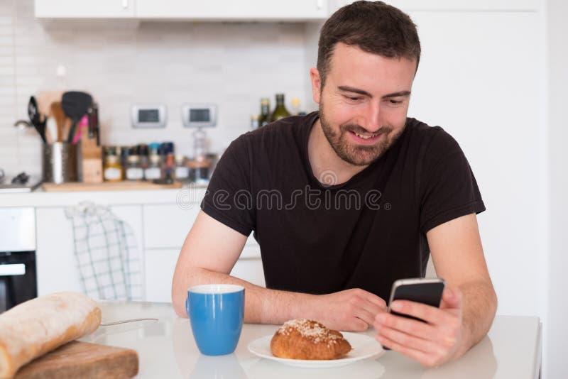 Het nieuws van de mensenlezing op zijn mobiele telefoon in de ochtend royalty-vrije stock foto