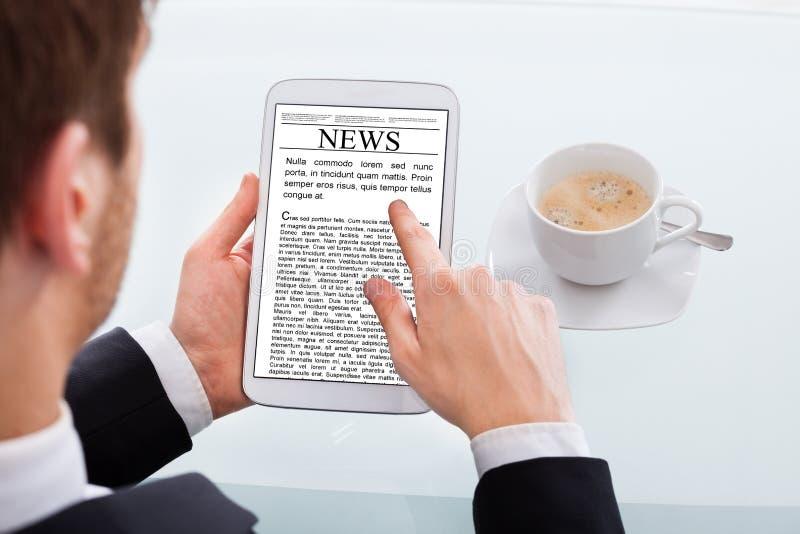 Het nieuws van de zakenmanlezing op digitale tablet bij bureau stock fotografie