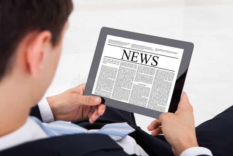 Het nieuws van de zakenmanlezing op digitale tablet in bureau stock afbeeldingen