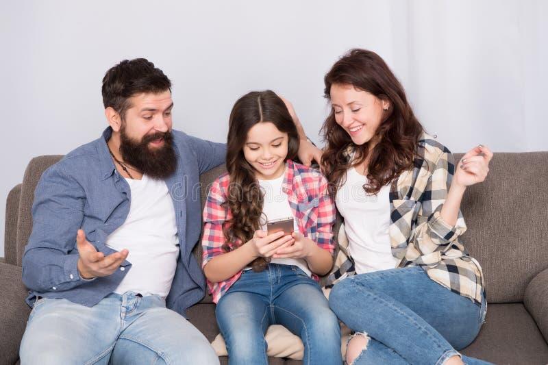 Het nieuws van het kindaandeel met moeder en vader Het gebruiks mobiele telefoon van het meisjekind Gelukkige Familie thuis Koop  royalty-vrije stock foto