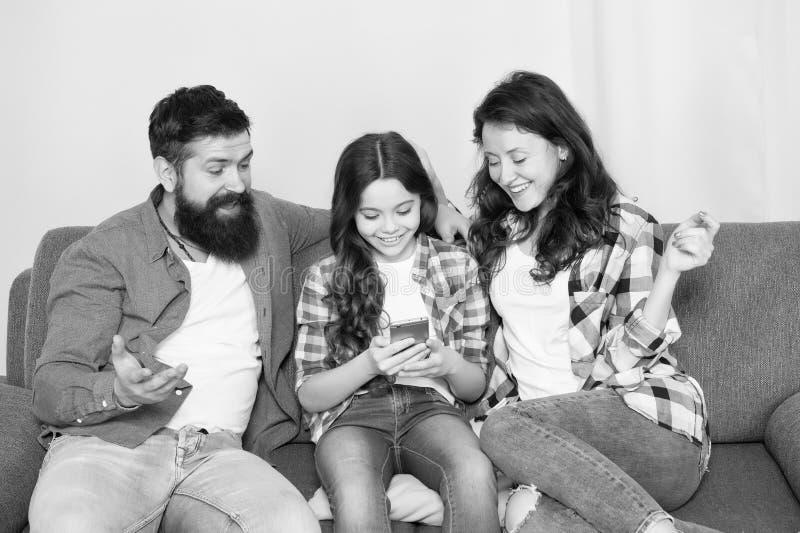 Het nieuws van het kindaandeel met moeder en vader Het gebruiks mobiele telefoon van het meisjekind Gelukkige Familie thuis Koop  royalty-vrije stock afbeelding