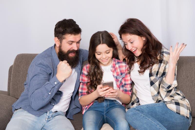 Het nieuws van het kindaandeel met moeder en vader Het gebruiks mobiele telefoon van het meisjekind met ouders Gelukkige Familie  royalty-vrije stock afbeeldingen