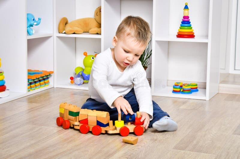 Het nieuwsgierige kind spelen met een trein royalty-vrije stock foto