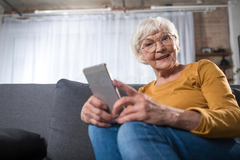Het nieuwsgierige slimme oude vrouw ontspannen thuis met mobiel apparaat stock fotografie