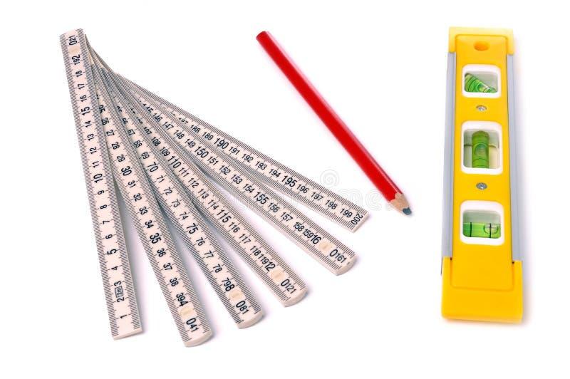 Het niveau van de maatregel, van het potlood en van de bel stock foto's