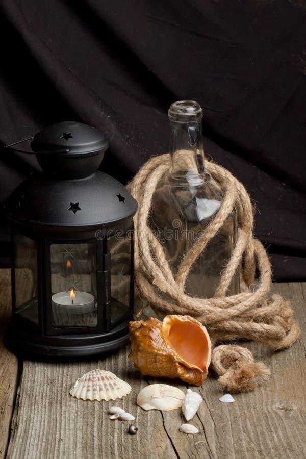 Het nog-leven met oude lantaarn, flessen en overzeese shells stock afbeeldingen