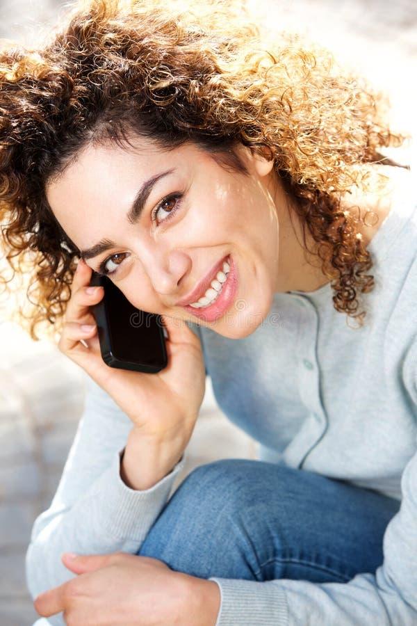 Het noorden Afrikaanse vrouw die en op mobiele telefoon glimlachen spreken royalty-vrije stock afbeelding