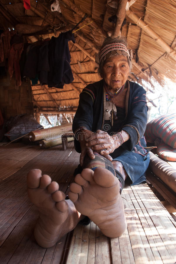 Het noorden van Thailand tijdens de hete zomer Een oude vrouw van de etnische Groep van Akha, rust in de schaduw van haar die hui royalty-vrije stock afbeelding