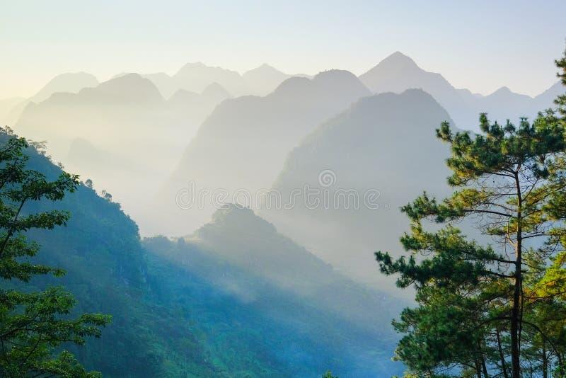 Het noorden Vietnamese die vallei met karst bergen door mist in Ha Giang/Dong Van-gebied worden behandeld stock afbeeldingen