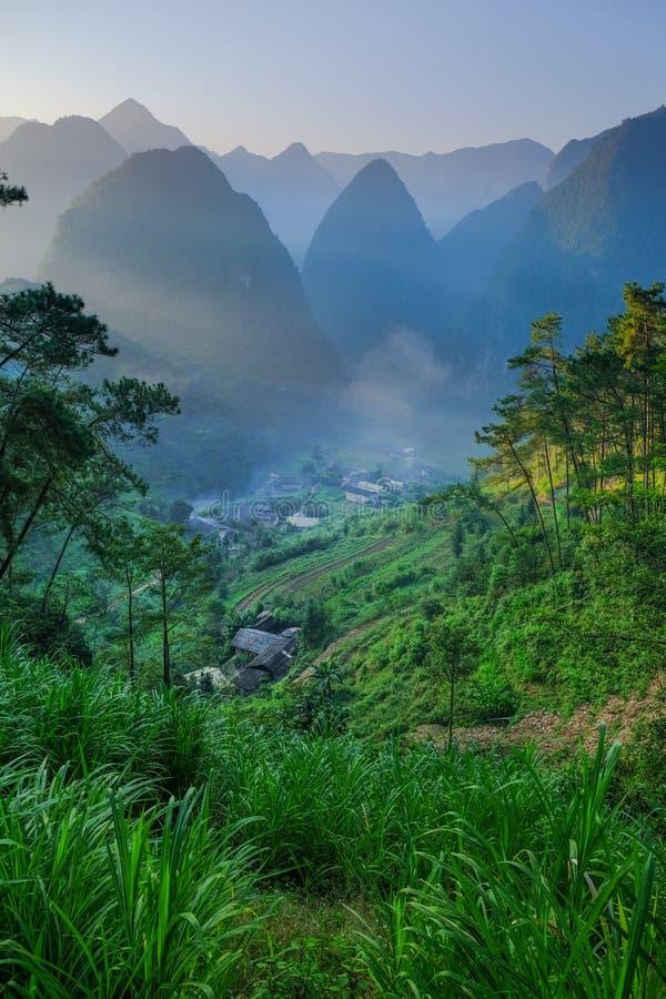 Het noorden Vietnamese die vallei met karst bergen door mist in Ha Giang/Dong Van-gebied worden behandeld stock foto