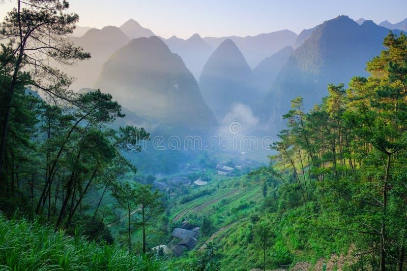 Het noorden Vietnamese die vallei met karst bergen door mist in Ha Giang/Dong Van-gebied worden behandeld stock foto's