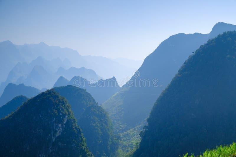 Het noorden Vietnamese die vallei met karst bergen door mist in Ha Giang/Dong Van-gebied worden behandeld stock afbeelding
