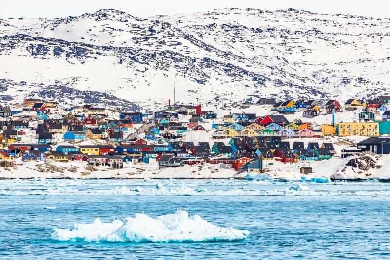 Het noordpoolpanorama van de sneeuwstad met kleurrijke Inuit-huizen op de rots royalty-vrije stock afbeeldingen