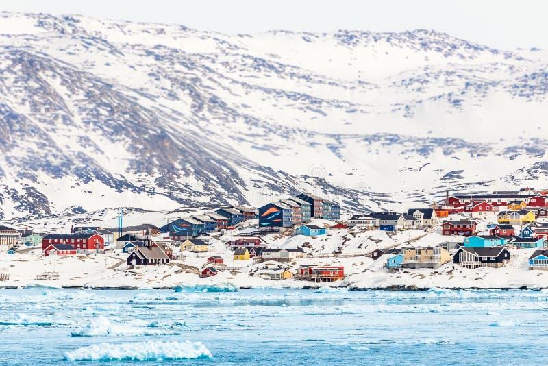 Het noordpoolpanorama van de sneeuwstad met kleurrijke Inuit-huizen op de rots stock afbeeldingen