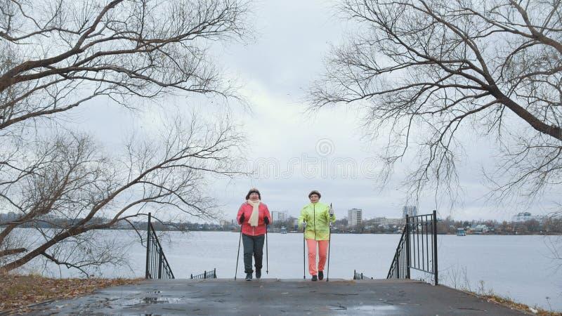 Het noordse lopen voor bejaarden openlucht - twee hogere dames hebben opleiding openlucht stock fotografie