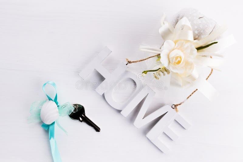Het noordse stijlstilleven op een witte houten achtergrond met houten brieven met het inschrijvingshuis en de sleutels huisvesten royalty-vrije stock foto's